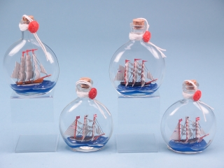 Assortment of four Ships in Small Round Bottles. 10cm. Wax sealed.